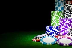堆在一张绿色赌博啤牌桌上的纸牌筹码在赌博娱乐场 扑克牌游戏概念 打与模子的一场比赛 赌博娱乐场概念 免版税图库摄影