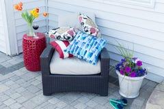 堆在一把室外扶手椅子的五颜六色的坐垫 免版税库存图片