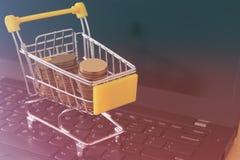 堆在一辆台车的硬币在膝上型计算机键盘 做金钱或购物网上,电子商务概念 库存照片
