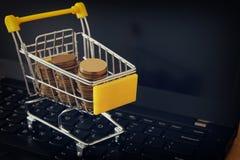 堆在一辆台车的硬币在膝上型计算机键盘 做金钱或购物网上,电子商务概念 免版税图库摄影