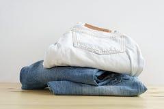 堆在不同颜色的牛仔裤在木桌纹理 库存照片