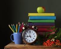 堆在五颜六色的盖子、铅笔、闹钟和胸罩的书 免版税库存照片