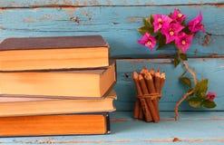 堆在五颜六色的铅笔旁边的旧书和九重葛在木桌上开花 葡萄酒被过滤的图象 免版税库存图片
