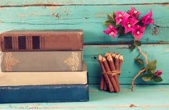堆在五颜六色的铅笔旁边的旧书和九重葛在木桌上开花 葡萄酒被过滤的图象 库存图片