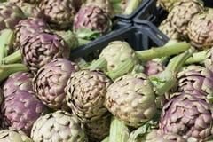 堆在农夫marke的绿色和紫色意大利朝鲜蓟 免版税图库摄影