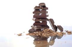 堆在反射性玻璃的巧克力 库存照片