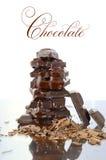 堆在反射性玻璃的巧克力 库存图片