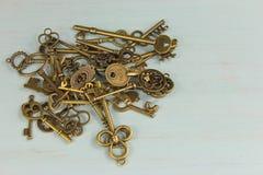 堆在困厄的木背景的古色古香的黄铜钥匙 库存图片