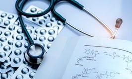 堆在天线罩包装的片剂药片与药物结构书和听诊器在白色背景 诊断的医疗设备 免版税图库摄影