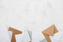 堆在工作桌面看法的五颜六色的信封 企业邮件, blogging和办公室书信背景 平的位置 免版税库存图片