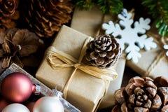 堆在工艺纸五颜六色的球大和小杉木锥体绿色杉树分支包裹的圣诞节和新年礼物盒 库存图片