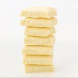 堆在平衡的巧克力片;在白色 免版税库存图片