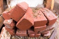 堆在建造场所几何畸变白点的红砖 免版税库存照片