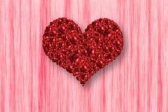 堆在心脏形状的红色玫瑰在桃红色背景 库存照片