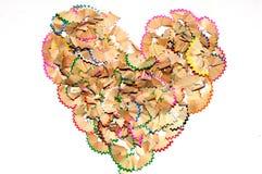 堆在心脏形状的五颜六色的铅笔削片 库存图片
