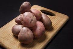 堆在木书桌上的土豆有黑背景 库存照片