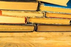 堆在木桌上的书 免版税库存照片