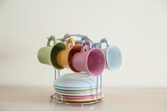 堆在木桌上的五颜六色的咖啡杯 免版税图库摄影