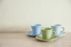 堆在木桌上的五颜六色的咖啡杯 图库摄影
