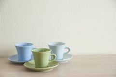 堆在木桌上的五颜六色的咖啡杯 免版税库存图片