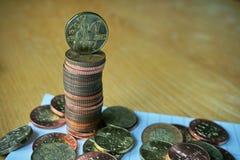 堆在木桌上的硬币与一枚金黄捷克冠硬币按20 CZK的价值在上面的 免版税图库摄影