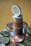 堆在木桌上的硬币与在上面的一枚金黄欧洲硬币 库存图片