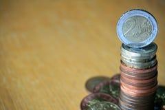 堆在木桌上的硬币与在上面的一枚金黄欧洲硬币 免版税图库摄影
