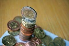 堆在木桌上的硬币与在上面的一枚金黄欧洲硬币 免版税库存照片