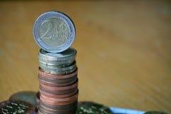 堆在木桌上的硬币与在上面的一枚金黄欧洲硬币 免版税库存图片
