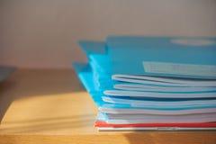 堆在木桌上的蓝色笔记本 免版税库存照片