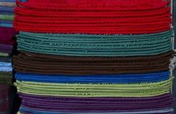 堆在架子以各种各样的颜色堆积的地板席子 库存照片