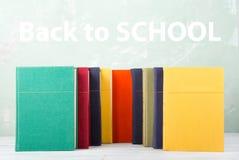 堆在架子和绿色背景的老色的书与文本& x22; 回到school& x22; 免版税图库摄影