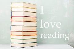 堆在架子和绿色背景的老色的书与文本& x22; 我爱reading& x22; 库存图片