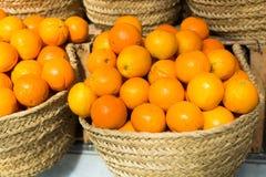 堆在柳条筐的水多的桔子在市场柜台 库存照片