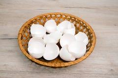 堆在柳条筐的空的白鸡蛋壳 免版税图库摄影