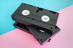 堆在桃红色和蓝色背景的3卷VHS磁带 免版税库存图片