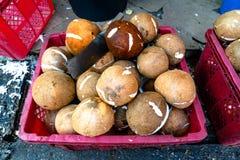 堆在桃红色塑料篮子的成熟或老椰子在市场上 免版税库存照片