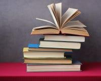 堆在桌上的书与一张红色桌布 图库摄影
