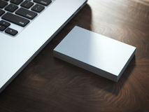 堆在桌上的名片在膝上型计算机附近 免版税库存照片
