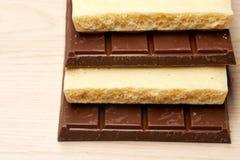 堆在桌上的黑暗和白色巧克力 免版税库存照片