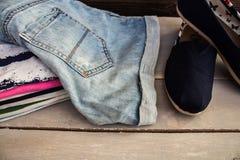 堆在桌鞋子的衣物 库存图片