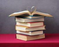 堆在桌,在上面的一本开放书上的书 库存图片