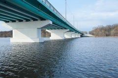 堆在桥梁下 横跨一条宽河的长的具体桥梁在一个晴天 库存照片