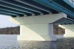 堆在桥梁下 横跨一条宽河的长的具体桥梁在一个晴天 免版税库存图片