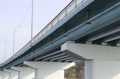 堆在桥梁下 横跨一条宽河的长的具体桥梁在一个晴天 免版税图库摄影
