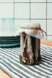 堆在毛巾的串包裹的瓶子的咸鱼与板材 免版税库存图片
