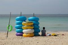 堆在海滩的五颜六色的浮动游泳圆环,橡胶swimmi 免版税库存照片