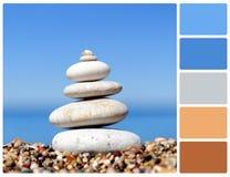 堆在海滩的小卵石石头与调色板颜色样片 免版税库存照片