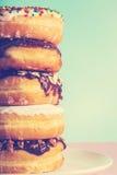 堆在淡色蓝色和桃红色背景的被分类的油炸圈饼 库存照片