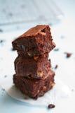 堆在淡色蓝色背景的巧克力果仁巧克力 库存图片